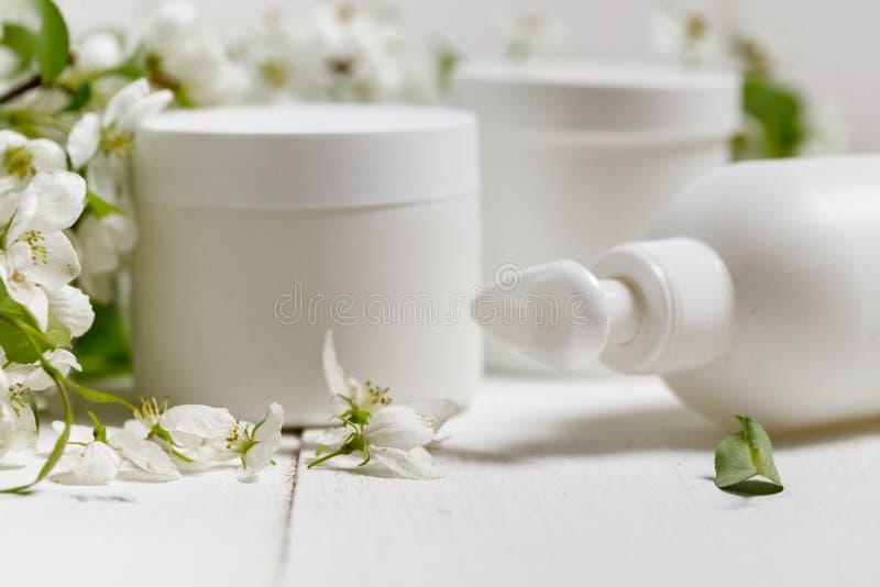 Набор ‹â€ ‹packaging†‹care†‹Skin†с предпосылкой ‹white†‹on†цветков весны бутылка пробела ‹â€ косметические/трубка moist стоковое изображение rf