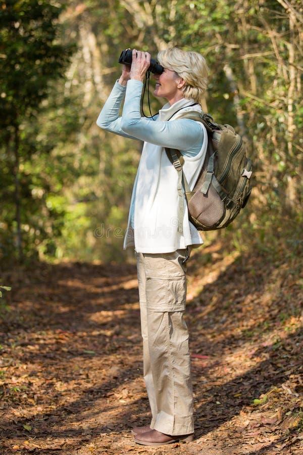 Наблюдать птицы биноклей женщины стоковое изображение