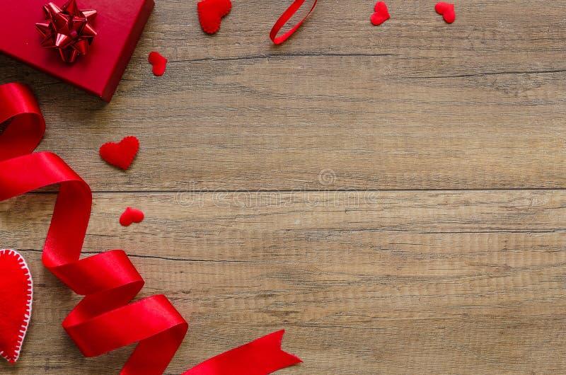 Наверху плоско положенная предпосылка дня валентинки Красные сердца, подарочная коробка и лента на деревянной затрапезной предпос стоковые фото