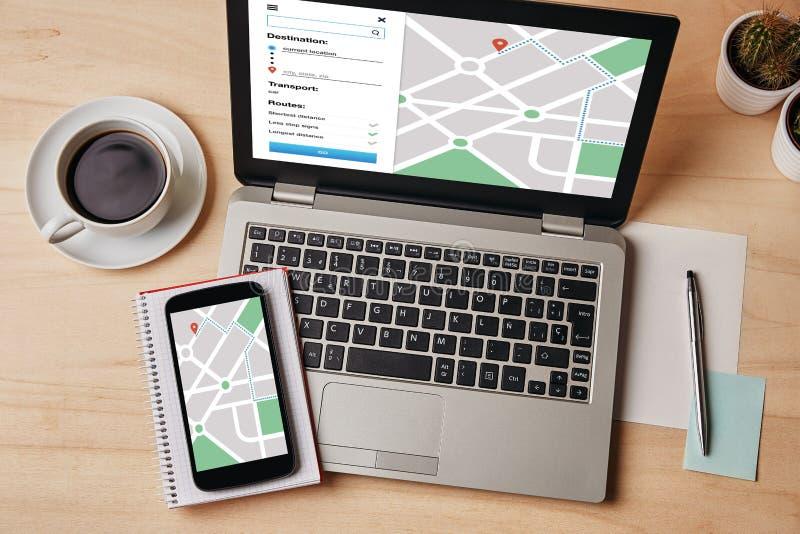 Навигация app карты GPS на экране компьтер-книжки и smartphone положение стоковые фотографии rf