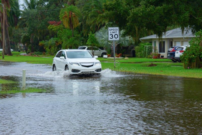 Наводнения и штормовые волнения в жилых районах, затопленных из-за движения автомобиля через глубину воды стоковое изображение