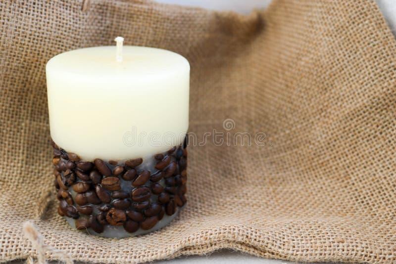 Навощите красивую светлую бежевую свечу при unflavored фитиль снизу украшенный с кофейными зернами на предпосылке старого коричне стоковые изображения rf