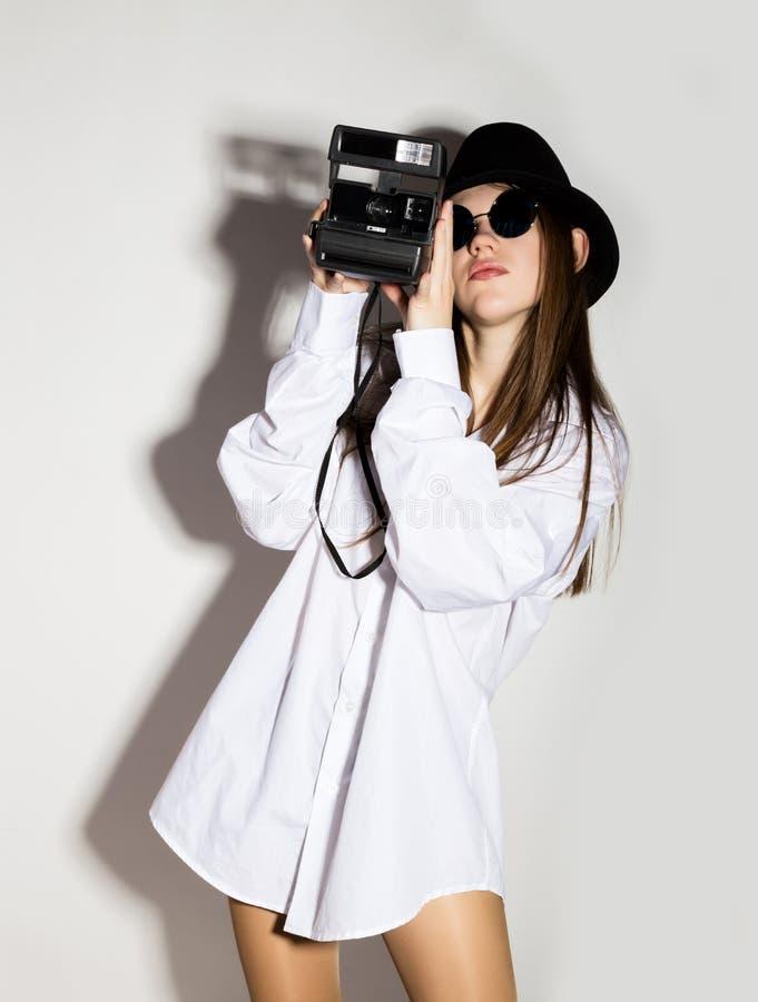 Нагая девушка в рубашке, солнечных очках и черной шляпе ` s человека белой, держа камеру стоковое изображение rf