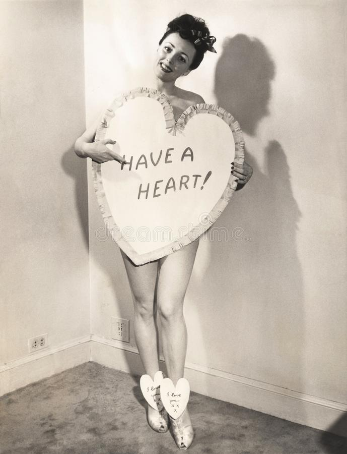 Нагая женщина предусматриванная в форме сердц знаком стоковые фото