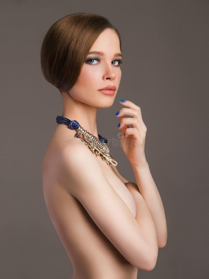 Нагая красивая девушка с ювелирными изделиями стоковые фото