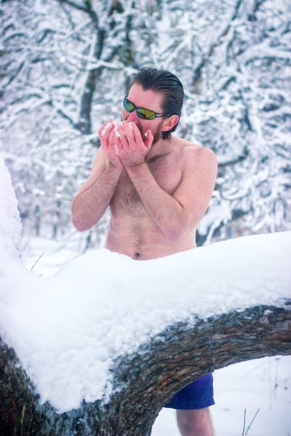 Нагой человек с солнечными очками в лесе зимы есть снег стоковое фото rf