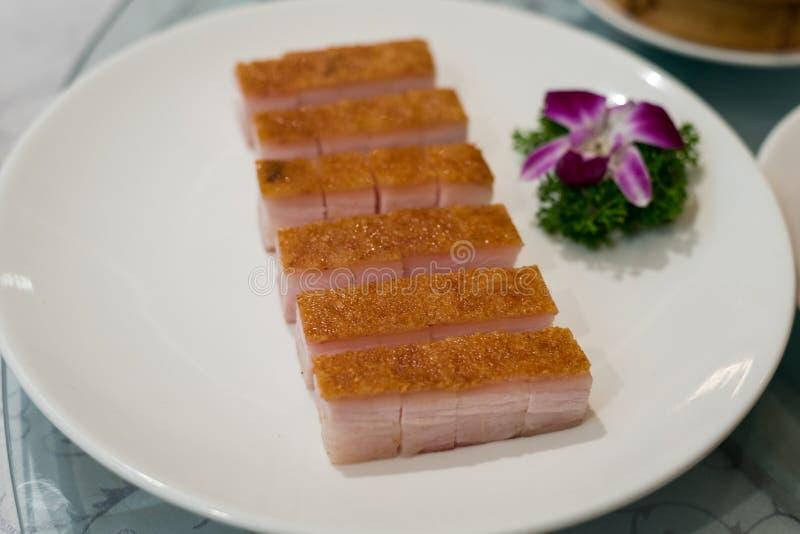 Наградной китайский кудрявый зажаренный в духовке свинина живота в белых блюдах на хие стоковое фото rf