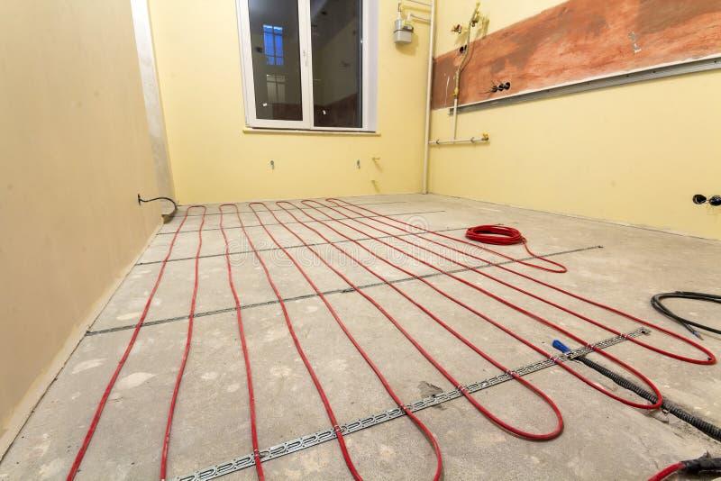 Нагревая красная установка провода электрического кабеля на пол цемента в небольшой новой незаконченной комнате с заштукатуренным стоковое изображение