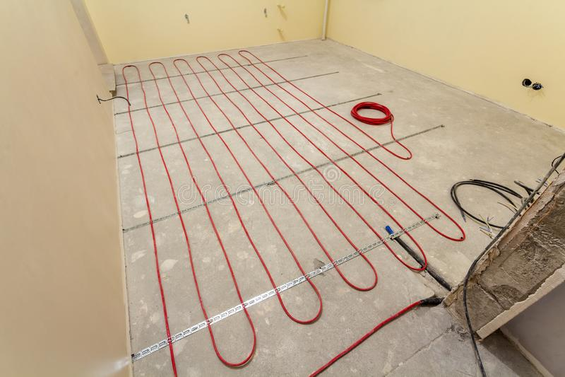 Нагревая красная установка провода электрического кабеля на пол цемента в небольшой новой незаконченной комнате с заштукатуренным стоковое изображение rf