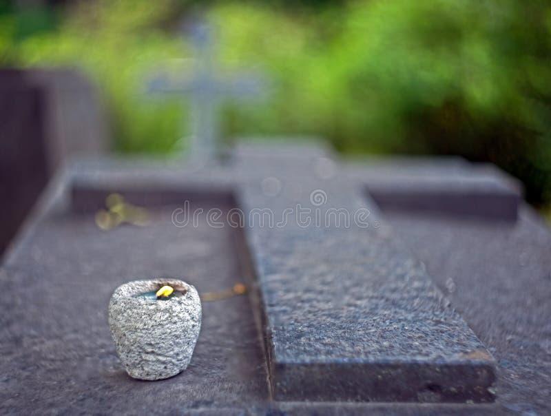 Надгробная плита гранита в форме креста с свечой стоковые фото