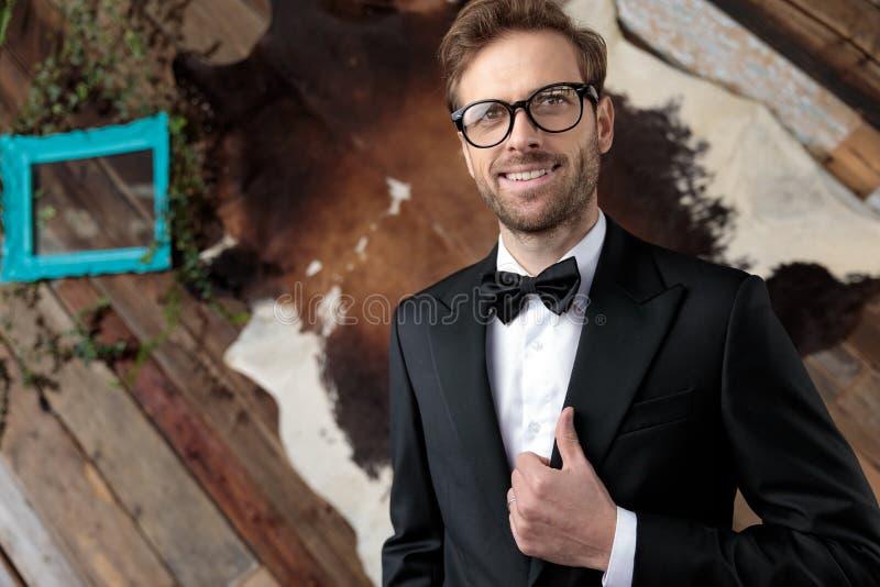 Надеждная модель моды, корректирующая его куртку и улыбающаяся стоковые фотографии rf