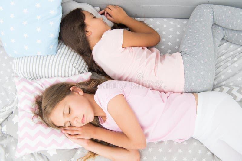 Надежная задняя часть здоровый детский сон лучшие друзья сестры в постели сладкие мечты маленькие девочки пижама в спальне детств стоковые фотографии rf