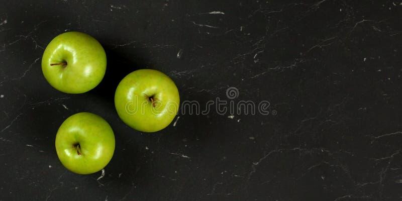 Надземная съемка, 3 зеленых яблока на черном мраморе как доска, широкое знамя с космосом для права текста стоковое фото