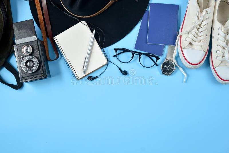 Надземный взгляд аксессуаров путешественника на голубой предпосылке с ретро камерой, шляпой, рюкзаком, eyeglasses, часами, ручкой стоковые изображения rf