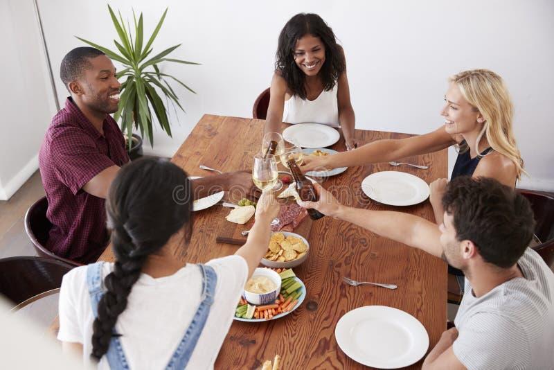 Надземный взгляд друзей наслаждаясь официальныйом обед дома совместно стоковое фото
