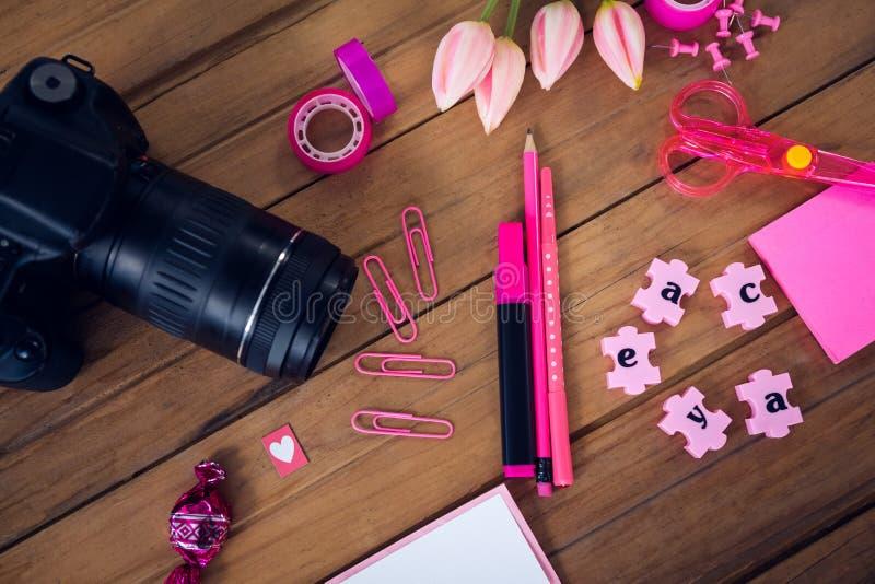 Надземный взгляд камеры с канцелярские товарами и искусственным тюльпаном цветет стоковая фотография
