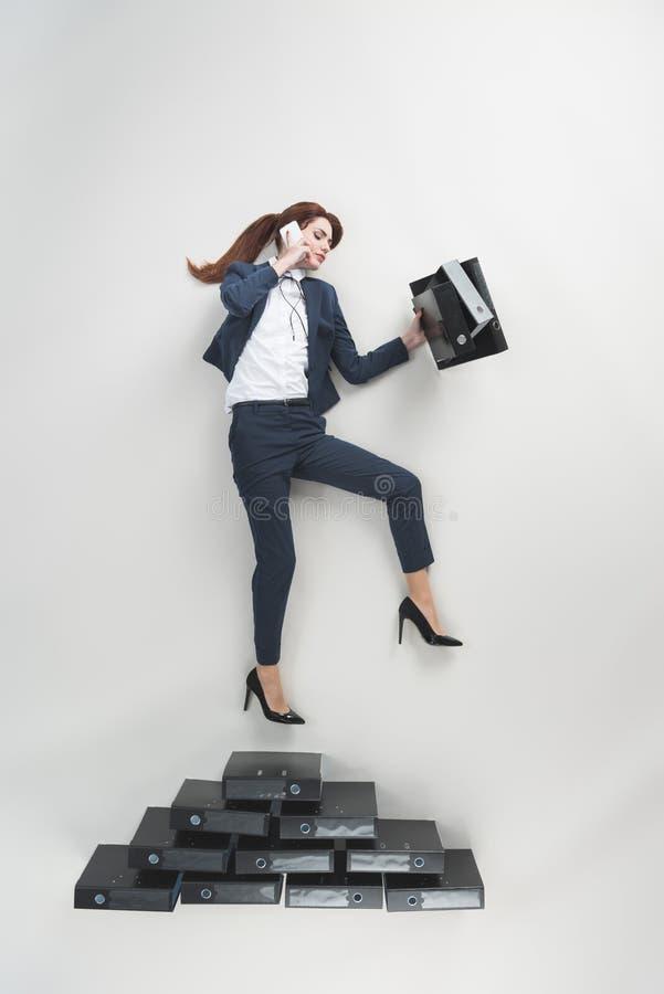 надземный взгляд коммерсантки с папками в руке говоря на smartphone стоковая фотография
