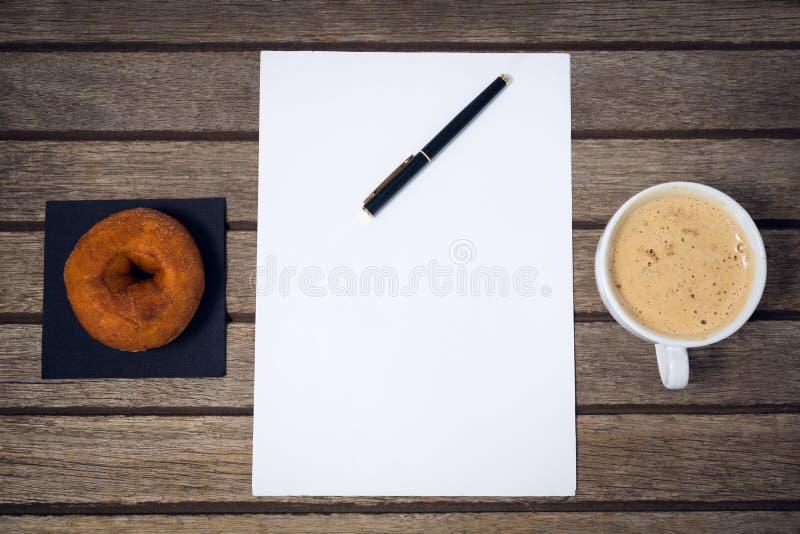 Надземный взгляд кофейной чашки с авторучкой на бумаге донутом стоковые фото