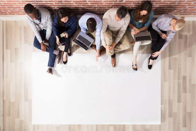 Надземный взгляд разнообразных людей с чистым листом бумаги стоковая фотография rf
