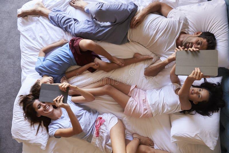 Надземный взгляд семьи лежа на кровати используя таблетки цифров стоковые изображения