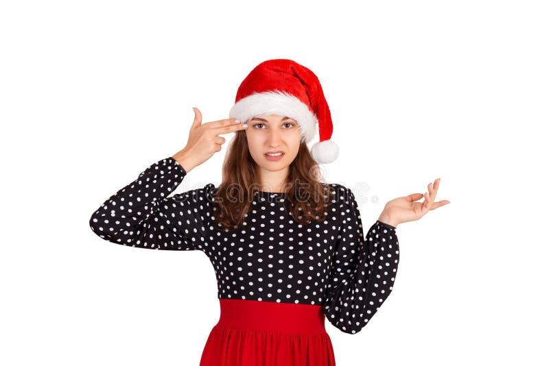 Надоеданная и раздражанная женщина в платье shrugging и держа пальцы на виске эмоциональная девушка в изоляте шляпы рождества Сан стоковые изображения rf