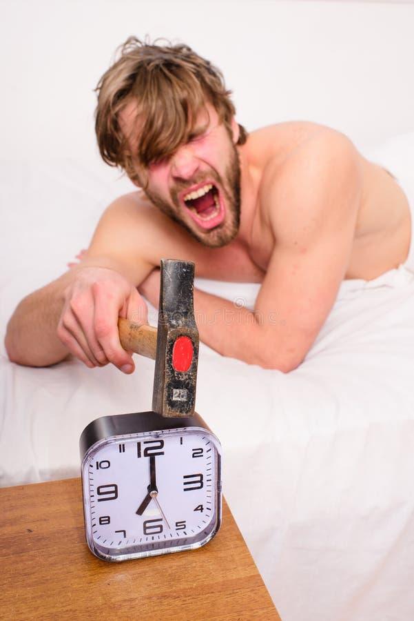 Надоедать звенящ каждое утро Сторона человека бородатая небритая надоеданная агрессивная кладет подушку около будильника Ломать Г стоковая фотография rf