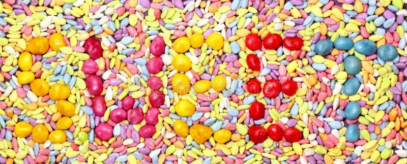 ` ` Надписи сладостное положено из студня конфеты на абстрактную яркую пестротканую прямоугольную предпосылку малых wi объектов стоковые фотографии rf