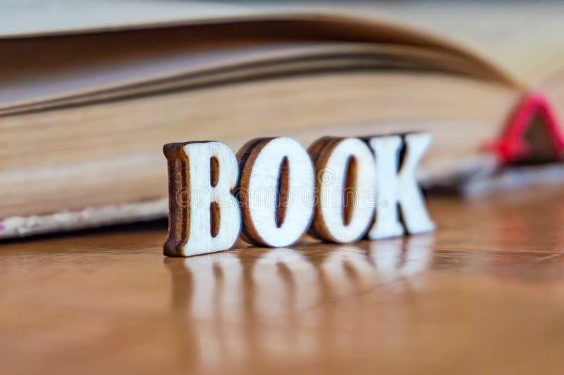 Надпись деревянных писем на предпосылке старой книги стоковая фотография