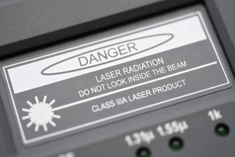Надпись когда измеряя радиация лазера опасности стекловолокна не смотрит внутри луча стоковые фотографии rf