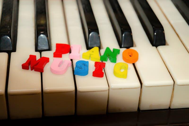 Надпись на ключах рояля в пестротканых письмах, музыки рояля стоковое фото rf