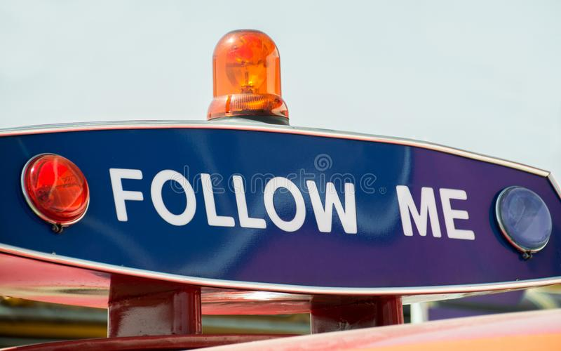 Надпись на ` полицейской машины следовать мной `, светосигнализатор мигающих огней красное голубого и оранжевого Требование остан стоковое фото