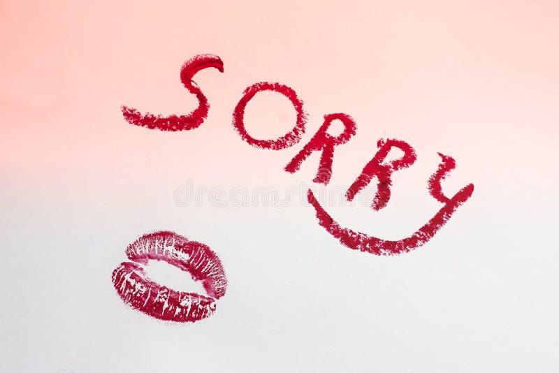 Надпись огорченная в красных письмах губной помады на розовом белом листе бумаги, печати губной помады в форме поцелуя стоковые изображения