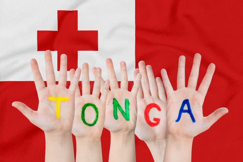 Надпись Тонга на руках детей на фоне развевая флага Тонги стоковые изображения rf
