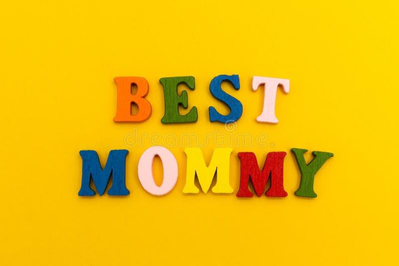 """Надпись """"самая лучшая мама """"в красочных письмах на желтой предпосылке стоковая фотография"""
