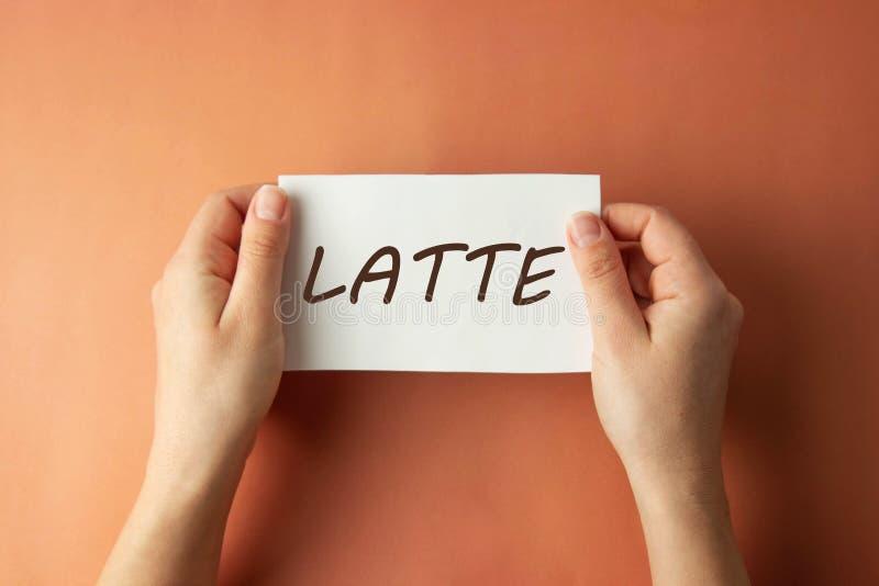 Надпись Latte Женщина держа бумагу с литерностью Latte в предпосылке изолированной руками коричневой Минималист тип стоковые фото