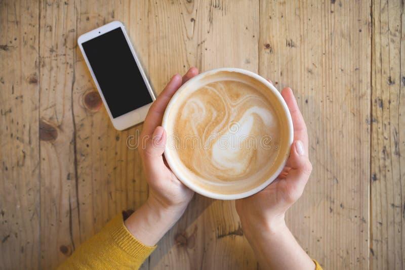 Над взглядом женских рук держа горячую чашку кофе и с умным телефоном стоковое фото