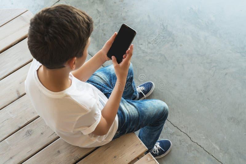 над взглядом Мальчик в белый сидеть футболки и солнечных очков крытом и smartphone польз Подросток играет компютерные игры стоковое изображение rf