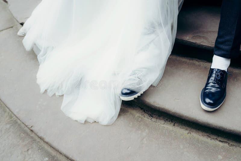 Над взглядом на ногах новобрачных на лестницах Посмотрите платья свадьбы kong ботинок жениха и невеста стоковые фото