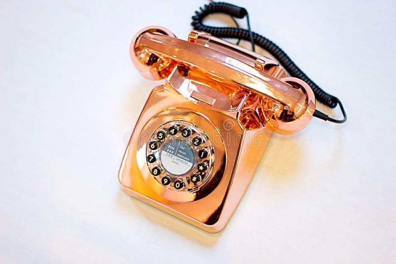 Над взглядом ретро телефона в почищенной щеткой меди с телефонной трубкой вниз стоковое фото rf