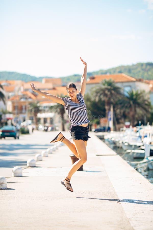 Над выведенной счастливой женщиной скача в воздух из счастья принципиальная схема часов предпосылки изолировала белизну стены кан стоковые изображения rf