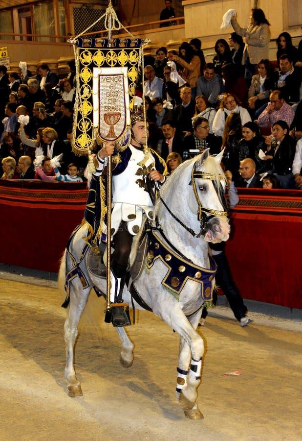 Наездник одетый как античный римский солдат легионера ехать красивая белая лошадь стоковая фотография