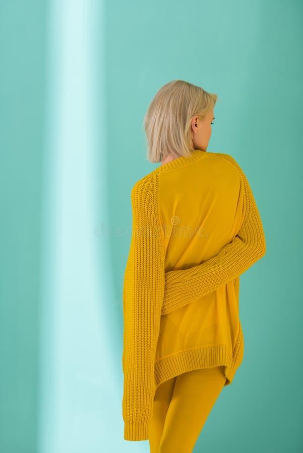 назад взгляд женщины в желтом свитере представляя на сини стоковое фото