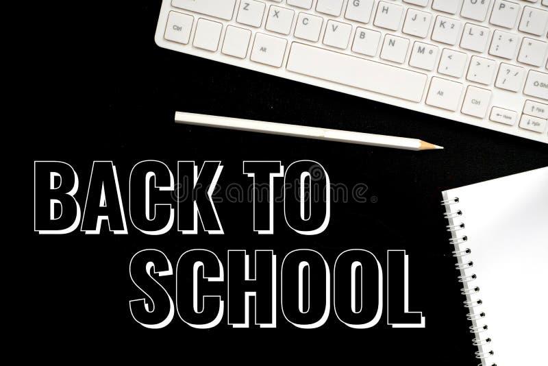 Назад в школу, текст над черной доской стоковое изображение