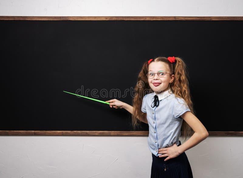 Назад в школу: Школьница девушки в школьной форме стоя на классн классном с указателем и шоу язык стоковые изображения