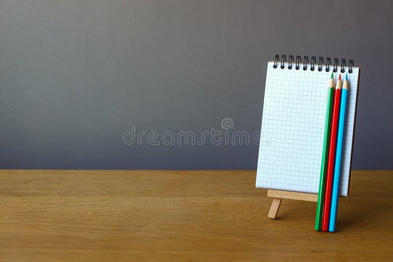 Назад до концепция школы, открытая тетрадь на миниатюрном мольберте и 3 покрашенных карандаша на деревянной поверхности на сером  стоковые изображения