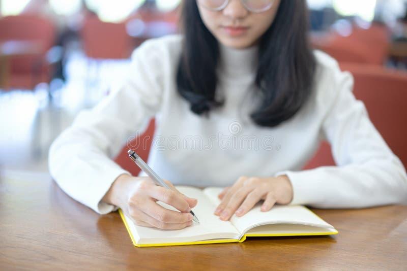 Назад к концепции университета коллежа знания школьного образования, молодая бизнес-леди сидя на таблице и принимая примечания в  стоковое изображение rf