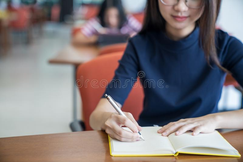 Назад к концепции университета коллежа знания школьного образования, молодая бизнес-леди сидя на таблице и принимая примечания в  стоковое фото