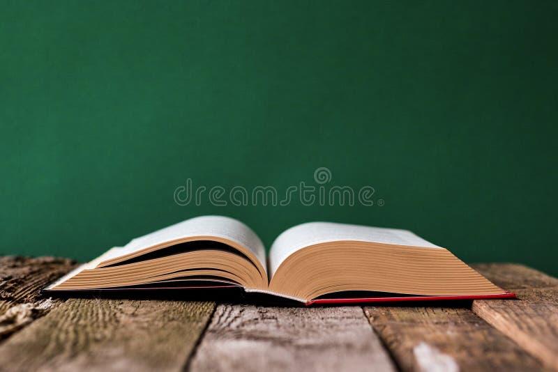 Назад к концепции школы, открытая книга на старой деревянной поверхности против фона чистой зеленой доски мела, выборочного фокус стоковое фото