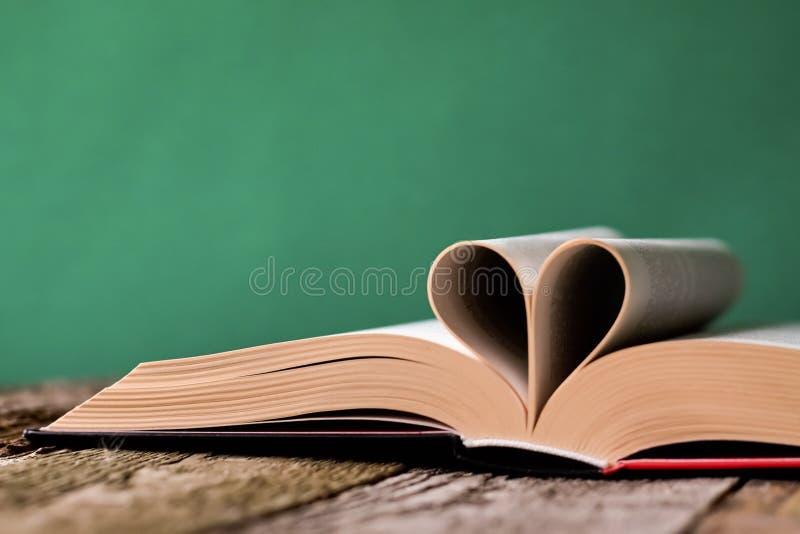 Назад к концепции школы, открытой книге и страницам сложенной в форме сердца на старой деревянной поверхности на фоне чистого зел стоковая фотография rf