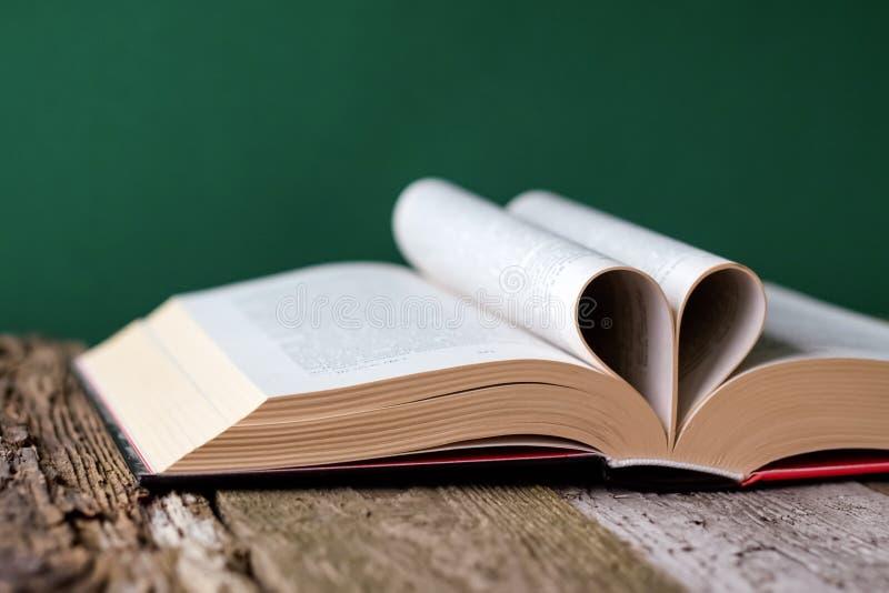 Назад к концепции школы, открытой книге и страницам сложенной в форме сердца на старой деревянной поверхности на фоне чистого зел стоковые изображения rf